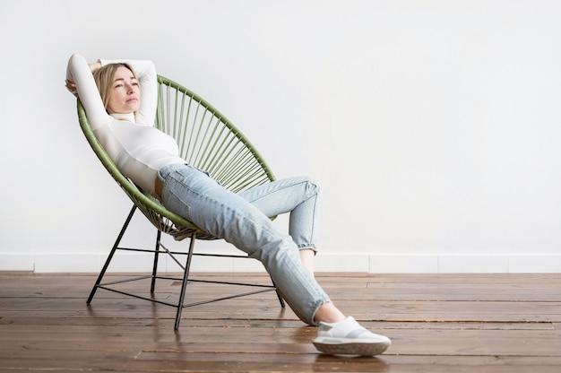 Donna che si siede su un colpo lungo della sedia
