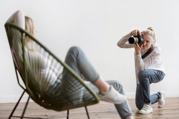 Donna che si siede su un concetto della fucilazione dello studio della sedia