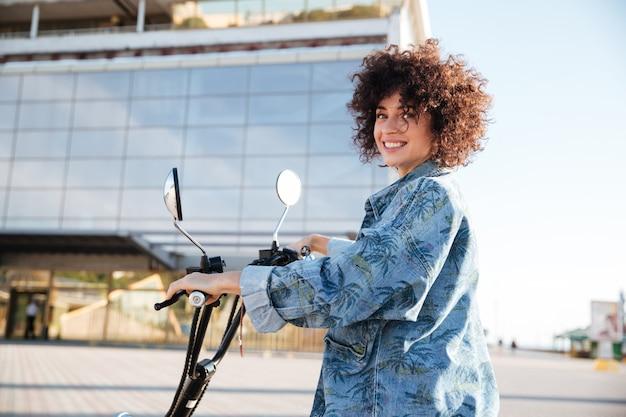Donna che si siede su una motocicletta all'aperto