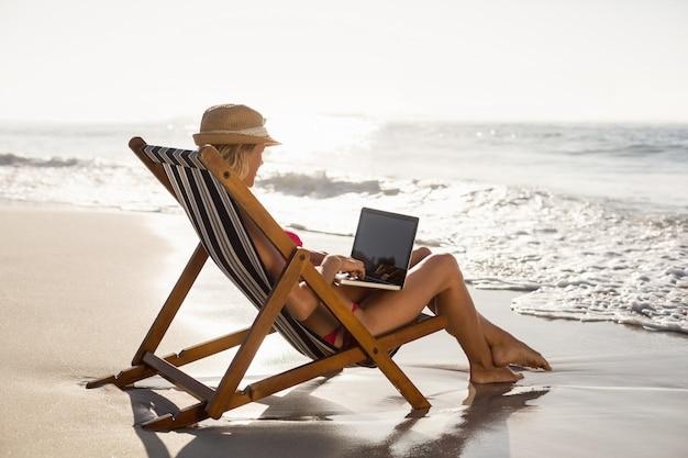 Donna che si siede su una poltrona e che per mezzo di un computer portatile