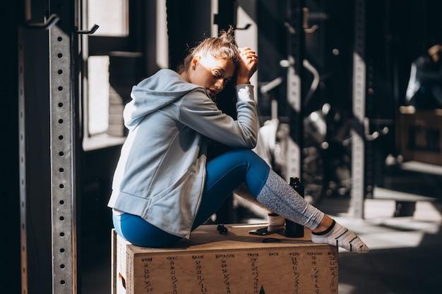 Donna che si siede su una scatola di legno a casa