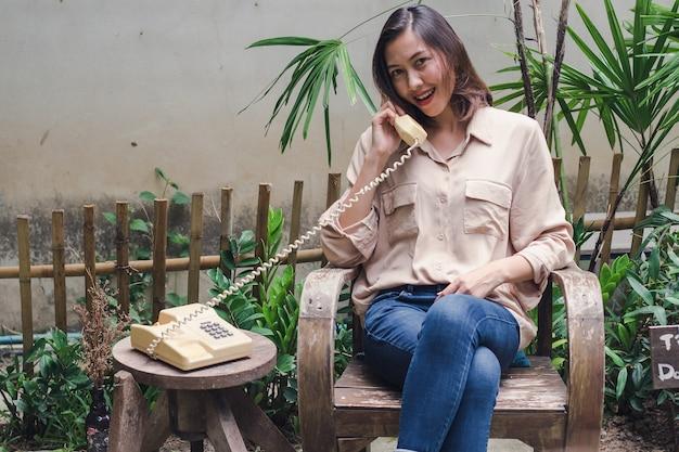Donna che si siede su una sedia di legno nel cortile