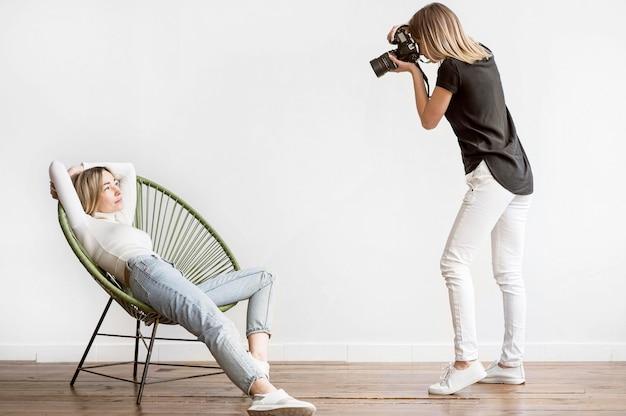 Donna che si siede su una sedia e un fotografo
