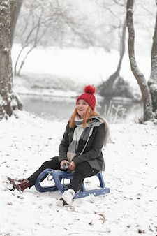 Donna che si siede su una slitta alla luce del giorno di inverno