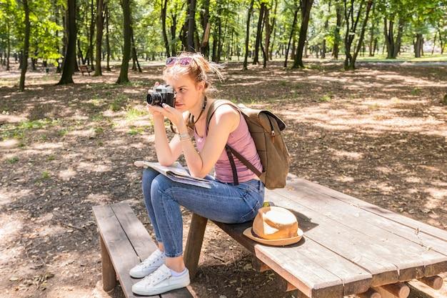 Donna che si siede su una tabella e che cattura una foto