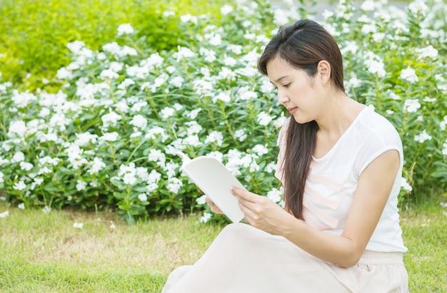 Donna che si siede sul campo in erba per la lettura del mattino