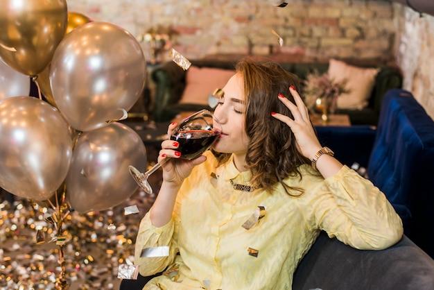 Donna che si siede sul divano bevendo vino in festa celebrazione