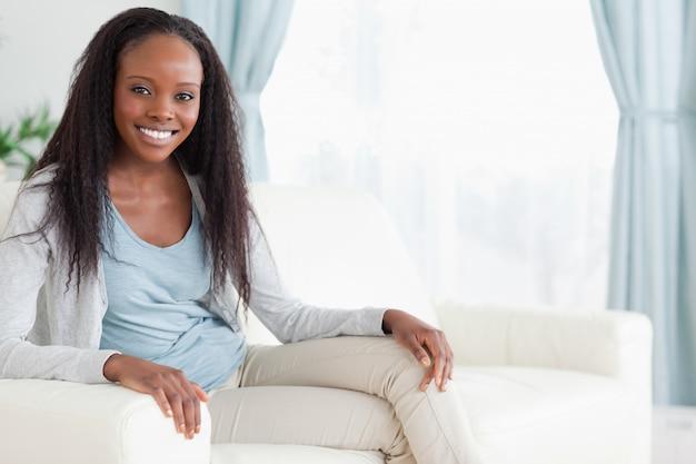 Donna che si siede sul divano con le gambe piegate