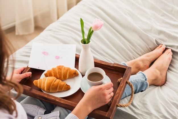 Donna che si siede sul letto con caffè sul vassoio