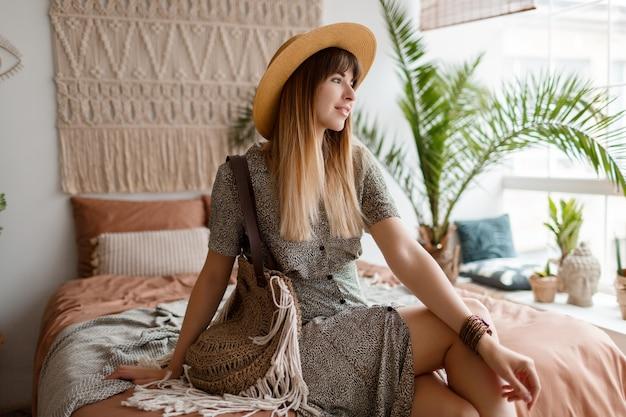 Donna che si siede sul letto nel suo appartamento di boho