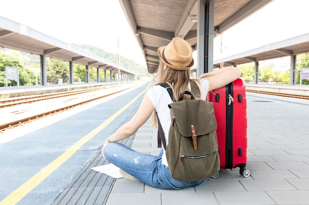 Donna che si siede sul pavimento alla stazione ferroviaria
