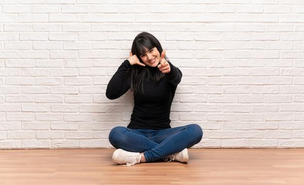 Donna che si siede sul pavimento che fa gesto del telefono e che indica fronte