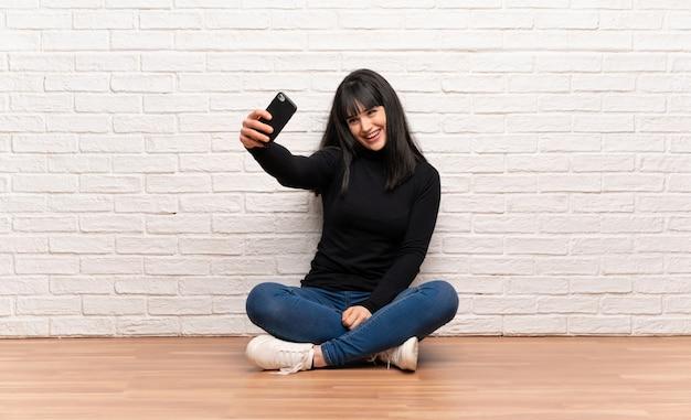 Donna che si siede sul pavimento che fa un selfie