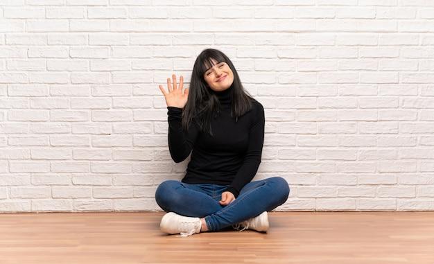 Donna che si siede sul pavimento che saluta con la mano con l'espressione felice