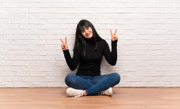 Donna che si siede sul pavimento che sorride e che mostra il segno di vittoria con entrambe le mani
