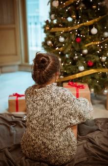 Donna che si siede sul pavimento vicino all'albero di natale