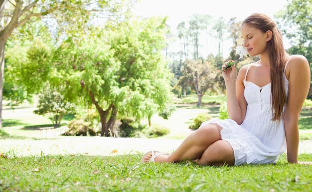 Donna che si siede sul prato mentre odorando un fiore