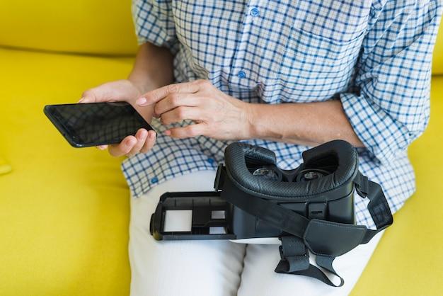 Donna che si siede sul sofà facendo uso del cellulare con la macchina fotografica virtuale sulle sue gambe