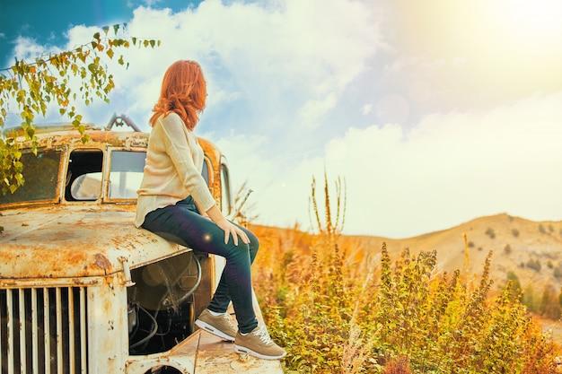 Donna che si siede sul vecchio camion classico arrugginito. giovane donna in un campo estivo seduto sulla vecchia auto.