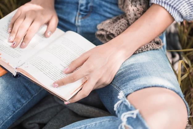 Donna che si siede sull'erba con il libro e seguendo il testo a mano