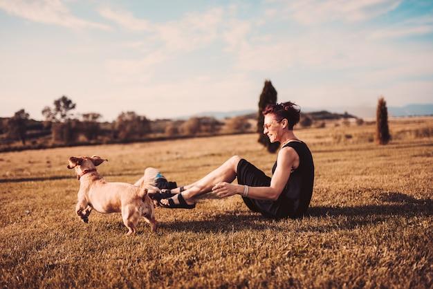 Donna che si siede sull'erba e che gioca con il cane