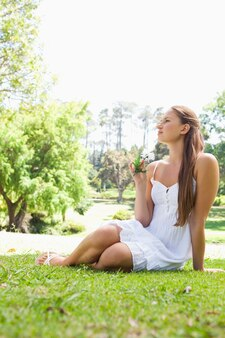 Donna che si siede sull'erba in un parco