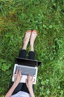 Donna che si siede sull'erba luminosa con il computer portatile
