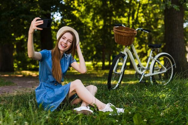 Donna che si siede sull'erba prendendo un selfie