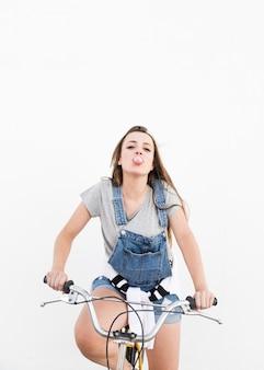 Donna che si siede sulla bicicletta che soffia di gomma da masticare rosa su fondo bianco