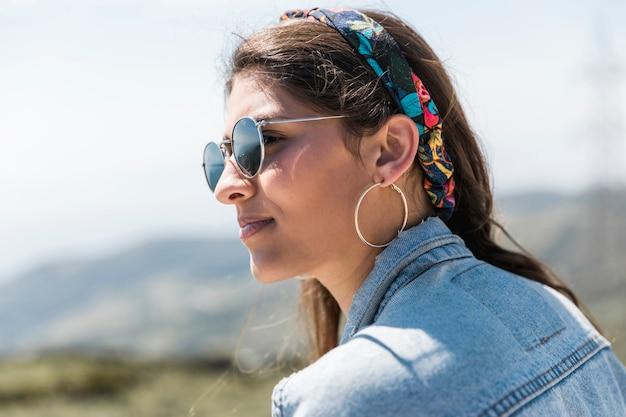 Donna che si siede sulla montagna e guardando lontano