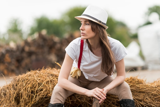 Donna che si siede sulla paglia in una fattoria