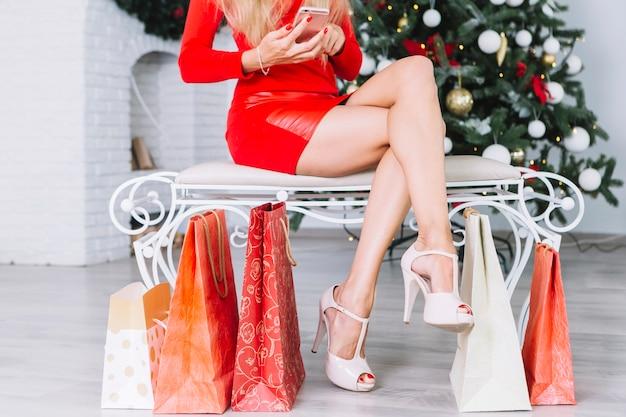 Donna che si siede sulla panchina con il telefono
