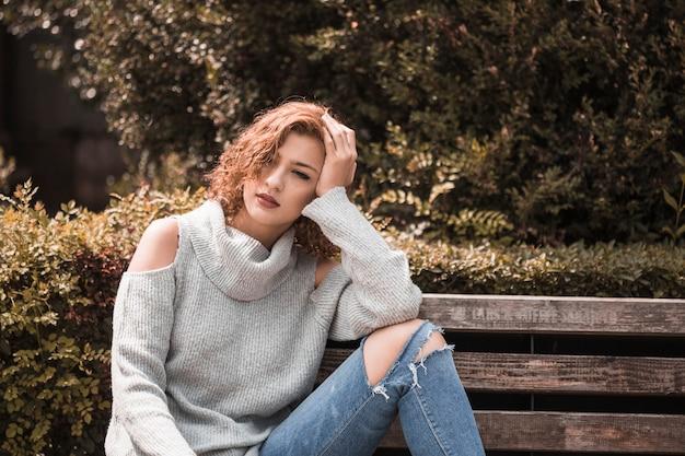 Donna che si siede sulla panchina nel parco