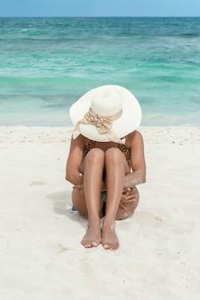 Donna che si siede sulla sabbia che abbraccia le sue gambe. donna in costume da bagno e cappello sulla spiaggia. swell. donna abbronzata abbronzatura. concetto di vacanza e relax