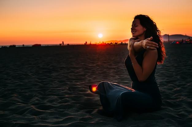 Donna che si siede sulla sabbia della spiaggia e rilassante al momento del tramonto