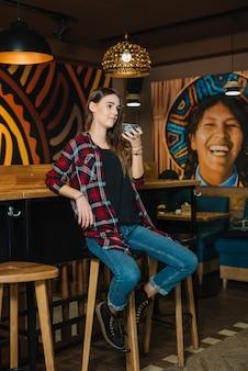 Donna che si siede sulla sedia della barra con caffè in caffè