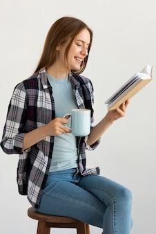 Donna che si siede sulla sedia durante la lettura di un libro