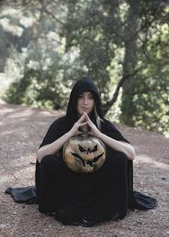 Donna che si siede sulla terra e che tiene zucca nel parco