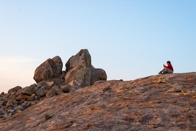 Donna che si siede sulle rocce e che esamina vista sopra il tempo scenico del deserto di namib al crepuscolo