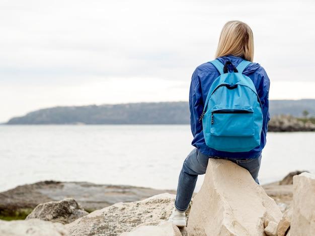 Donna che si siede sulle rocce