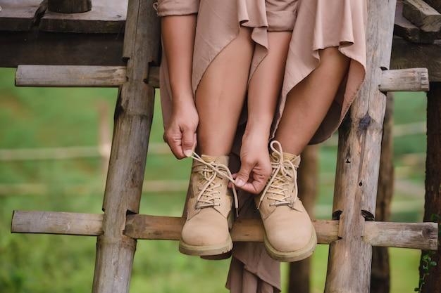 Donna che si siede sulle scale e che indossa stivali