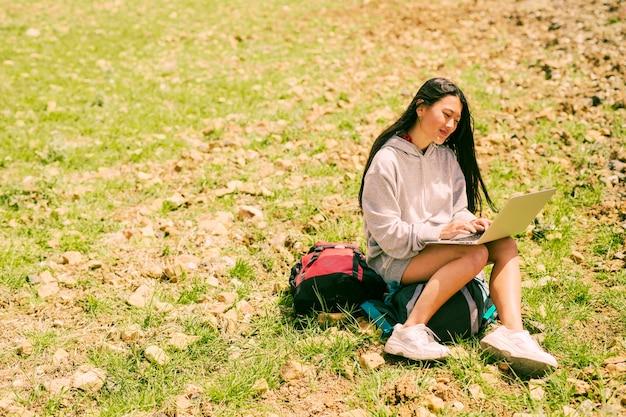 Donna che si siede sullo zaino che sorride e che lavora al computer portatile in collina verde