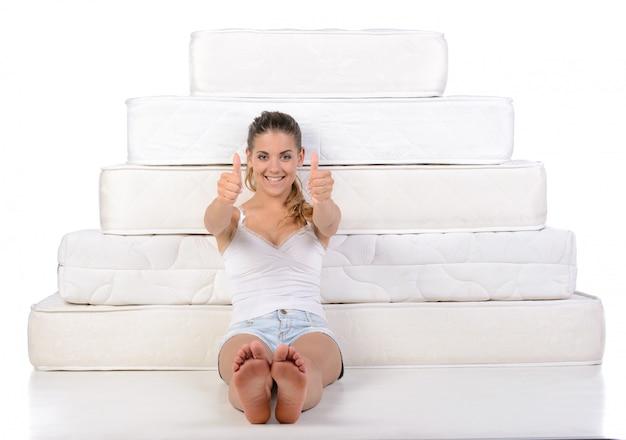 Donna che si siede vicino a molti materassi.