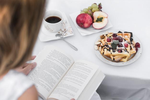 Donna che si siede vicino al libro di lettura del tavolo della colazione