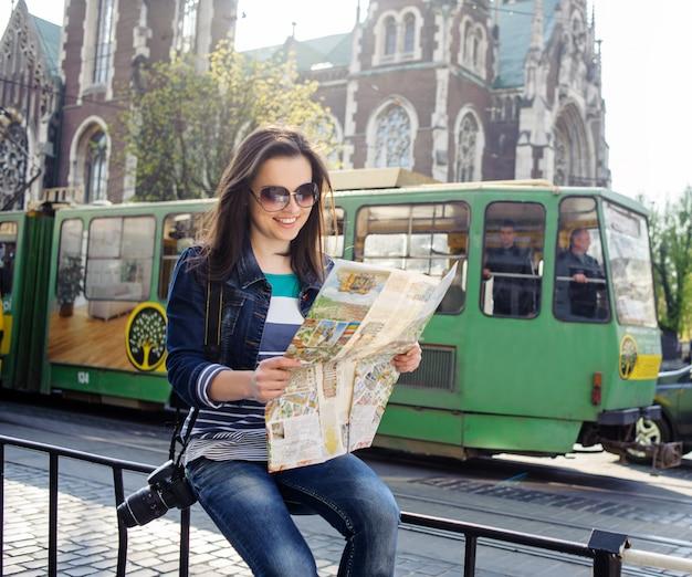 Donna che si siede vicino alla strada con la mappa nel vecchio centro urbano di leopoli