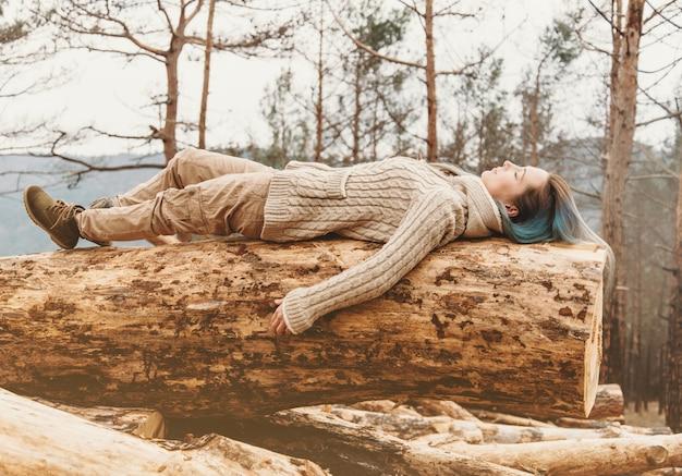 Donna che si trova sul tronco di albero all'aperto