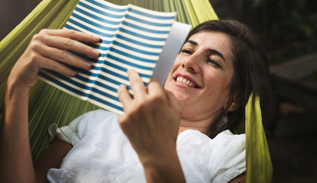 Donna che si trova sull'amaca che gelida libro di lettura