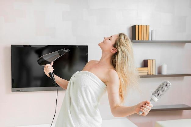 Donna che soffia i capelli con un asciugacapelli