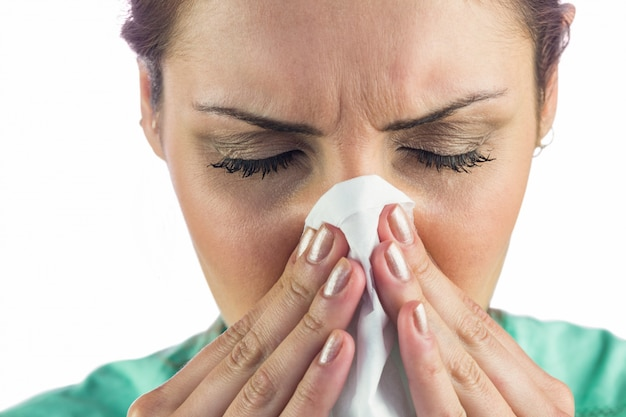 Donna che soffre di raffreddore con tessuto sulla bocca
