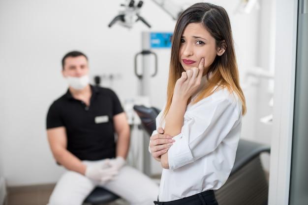 Donna che soffre di terribili dolori ai denti, toccando la guancia con la mano presso la clinica dentale.